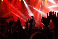 Angehobene Hände an einem Konzert Stockfoto