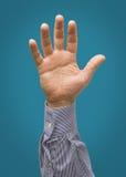 Angehobene männliche Hand lokalisiert auf blauer Knickente Lizenzfreie Stockfotografie