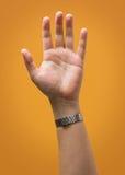 Angehobene männliche Hand lokalisiert auf gelbes Goldorange Stockfotografie