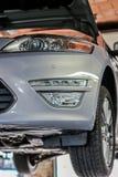 Angehobenes Auto in der Mechanikergarage stockbilder