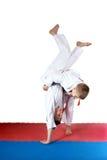 Angekleidet in den kleinen Athleten eines Kimonos bilden Sie Würfe aus Lizenzfreies Stockbild