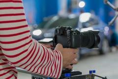Angekleidet in gestreiften langärmligen Fotograf ` s Händen halten eine Kamera auf einem unscharfen Hintergrund lizenzfreies stockbild