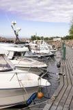 Angekoppelte Boote Verankerte Boote Boote, die in Folge an einem hölzernen Pier stehen Angekoppelte Boote lizenzfreie stockfotos