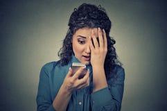Angelägen förskräckt ung flicka som ser telefonen som ser dåliga nyheterfotomeddelandet royaltyfri foto