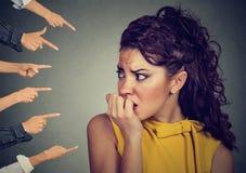 Angelägen kvinna som bedömas av olika folkfingrar som pekas på henne Arkivfoto