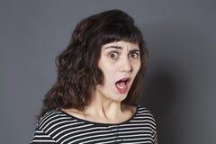 Angelägen ung brunettkvinna som ser förvånad Arkivbild
