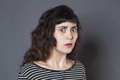 Angelägen ung brunettkvinna som ser skrämd Royaltyfri Fotografi