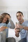 Angelägna män som håller ögonen på TV och har pizza med öl Arkivfoto