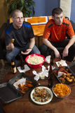 Angelägna två, medan hålla ögonen på sportar spela på TV, lodlinje Fotografering för Bildbyråer