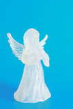 Angel. Glass white angel with wings on blue background Stock Image