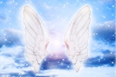 Angel. Wings over blue sky with divine light and stars Stock Photo