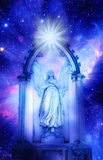 Angel. Arch standing in a gate over starry Universe with a rays of light Stock Photo