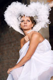 Angel. Beautiful female angel wearing white wings and long white tunic dress, sitting  on crashed brick wall and looking up with hope Stock Images