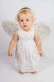 Angel. The small angel in a white dress looks in the camera Royalty Free Stock Images