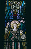 Angel 4. Detail of victorian stained glass church window in Fringford depicting a typical victorian angel with a lily in his hands royalty free stock photos