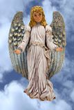Angel. Beautiful hand painted ceramic angel with arms out streached set against a blue sky filled with soft white clouds.Clipping path of the angel is included Stock Image