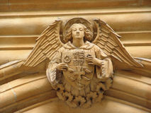 Angel on the arch with shield. Stone carving of angel on archway bearing shield royalty free stock images