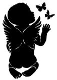 Angel baby with butterflies. Silhouette of kid smelling butterflies flying around him Royalty Free Stock Photography