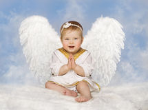 Angel Baby Wings, Angelic Cupid Toddler Kid Clasped Hands Folded. New Born Child Sitting at Blue Sky Cloud stock photos
