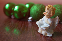 Angel on the background of Christmas balls. cristmas decoration. Christmas balls on a wooden table. Angel on the background of  green Christmas balls,new Year Stock Photo
