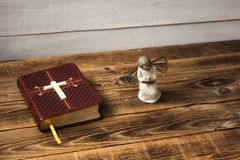 A angel bible and cross. On wooden background royalty free stock image