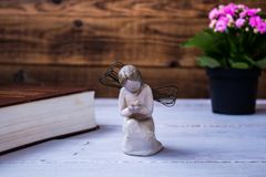 Angel and the bible and flowers. On wooden background Royalty Free Stock Images