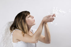 Angel blowing feathers off her hands Stock Photography