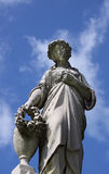 Angel on blue sky. An female angel statue with a blue sky background with clouds Stock Photo