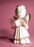 Angel with book. Little ceramic angel with book on a pink background Stock Photography
