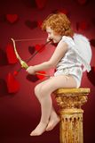 Angel boy. Profile of the small aiming boy - the cupid on a red background Stock Images
