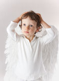 Angel boy. Beautiful little angel boy, white clothes, wings, blue eyes Royalty Free Stock Image