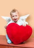 Angel boy. Laughing cute angel boy with big plush red heart. Copy space on the top right corner Royalty Free Stock Photography