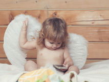 Angel boy with phone. Cute happy beautiful playful child boy with wet hair sitting in hothouse bath white fluffy towel naked indoor on wooden background in Stock Photo