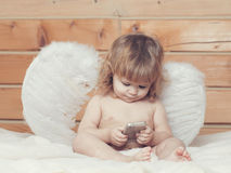 Angel boy with phone. Cute happy beautiful playful child boy with wet hair sitting in hothouse bath white fluffy towel naked indoor on wooden background in Royalty Free Stock Photos