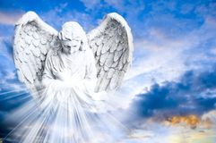 Angel bringing Light. A praying angel with beautiful wings with rays of divine light over blue cloudy sky with copy space Stock Images
