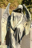Angel bronze sculpture at Monumental Cemetery, Milan. View of angel bronze sculpture at large monumental Cemetery in town, shot in bright late winter light  in Royalty Free Stock Photography