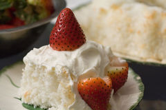 Angel Cake with Strawberries and Whipped Cream. A slice of angel food cake with strawberries and whipped cream on top, with a bowl of strawberries and the rest Stock Photography