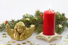 Angel with Candle and Fir. Golden angel with red candle and fir branch on light background Royalty Free Stock Images