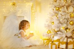 Angel Child and Christmas Tree with Presents Gifts, Kid Girl. Costume holding Candle Light stock photos