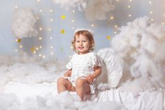 Angel child is sitting the clouds looks down stock image