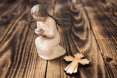 Angel and christian cross on wooden background Stock Image