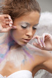 Angel in color make-up. Girl angel in color make-up poses Royalty Free Stock Photo