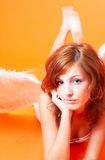 Angel With A Coy Smile. An angel laying on the ground with a coy smile royalty free stock photos