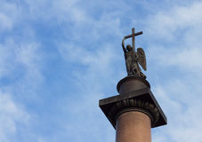 Angel with cross against cloudy blue sky Stock Image