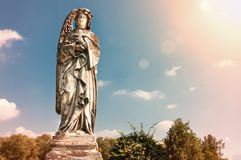 Angel with cross and sunlight against blue sky public sculpture at cemetery. Royalty Free Stock Photos