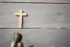 Angel and cross on wooden background stock photography