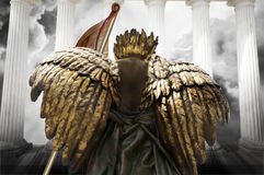 Angel. A dark golden winged angel with a staff banner stands in front of white columns and a stormy sky.  Religious warrior concept Royalty Free Stock Photos