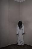 Angel of Death Horror. Vertical photo of a horrorful girl. Her hair is in front of her face, she looks creepy. She has wings of shadow. This is like a scene from stock photos