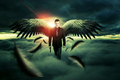 Angel of Death. Man with angel wings walking on clouds Stock Images