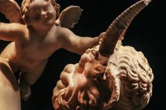 Angel and Devil - detail of ancient roman statue with cherub grabbing the horn of a satyr - selective focus on dark background.  royalty free stock photography